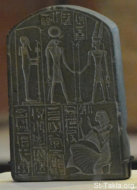 "St-Takla.org Image: Stele dedicated by Chia, treasurer of a temple of Ramses II, representing the gods of Thebes, Heliopolis and Memphis: Amun-Ra, Ra-Herakhty and Ptah. Greywacke, New Kingdom. Hieroglyphs, Column 2-(reads from left):"" 'Behold !', the Kingdom's scribe....""-behold is i-N, the reed and Red Crown; below is the ""sedge"", and Scribe equipment. (In top right)-God Amun-Ra is portrayed written as: ""Amun-Ra...Lord of the Thrones of the Two Lands"".-(the thrones are 3-Jar stands) - Greywacke; H. 12.8 cm (5 in.), 8.7 cm (3 ¼ in.); Department of Egyptian antiquities, Sully, first floor, room 38 - The Louvre Museum (Musée du Louvre), Paris, France - Photograph by Michael Ghaly for St-Takla.org, October 11-12, 2014 صورة في موقع الأنبا تكلا: لوحة نصب تذكاري تصور ""شيا"" خازن معبد رمسيس الثاني، وهو يقدم آلهة طيبة، هليوبوليس، ممفيس: الأله آمون رع، الإله رع، الإله بتاح. - مصنوعة من حجر الجرواق، المملكة الحديثة - صور متحف اللوفر (اللوڤر)، باريس، فرنسا - تصوير مايكل غالي لموقع الأنبا تكلاهيمانوت، 11-12 أكتوبر 2014"