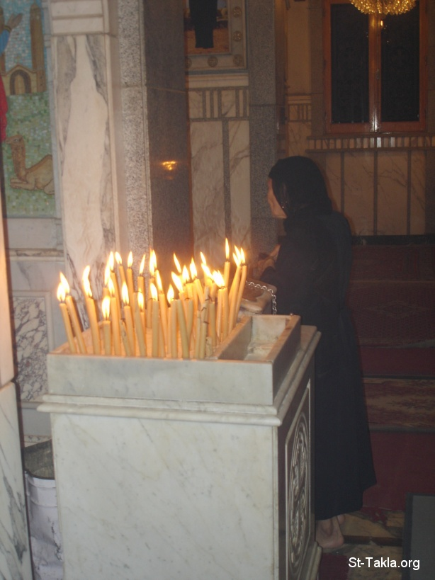 St-Takla.org Image: An old woman praying in front on an Coptic icon with candles, showing also an alms-giving box, poor widow - Photograph by Michael Ghaly for St-Takla.org صورة في موقع الأنبا تكلا: امرأة عجوز أو أرملة فقيرة تصلي أمام أيقونة قبطية، وأمامها الشموع، وصندوق العطاء - تصوير مايكل غالي لـ: موقع الأنبا تكلا هيمانوت